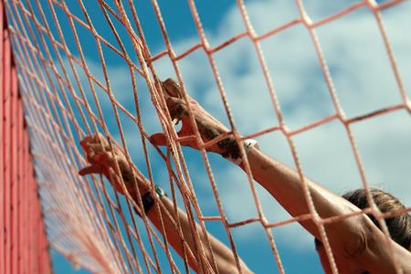 Mud race runners.Woman lying on the net