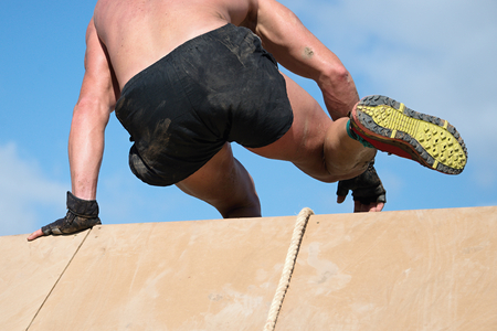 Man jumping over wall on obstacle course Stock Photo