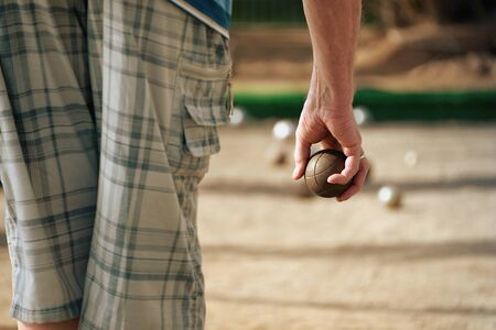 bocce: Senior men playing petanque, balls on the ground.