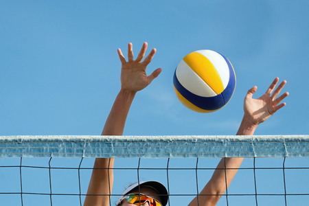 pelota de voley: Beach volley ball player jumps on the net and tries to blocks the ball