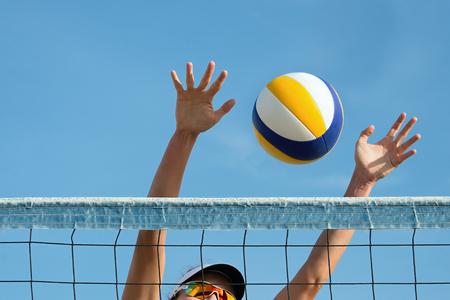 pelota de voley: Playa jugador de voleibol saltos en la red y trata de parar el bal�n