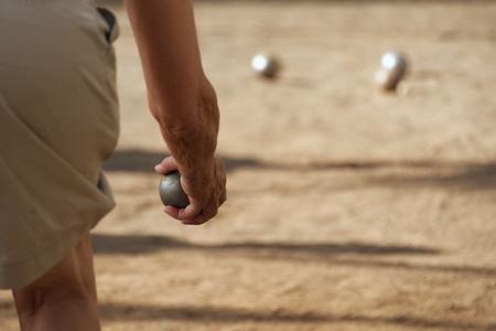 Senior playing petanque, balls on the ground