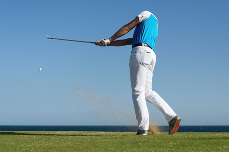 Golfer hitting ball with force. The grass distribution and ball blurred.