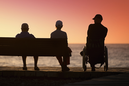 silhouette disabled man looks into the distance, enjoy summer on the ocean Stock Photo