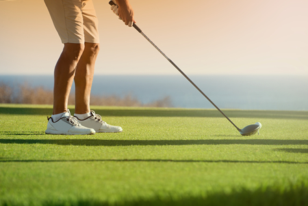 tee off: Golfer is going to tee off at sunset, ocean and horizon Stock Photo