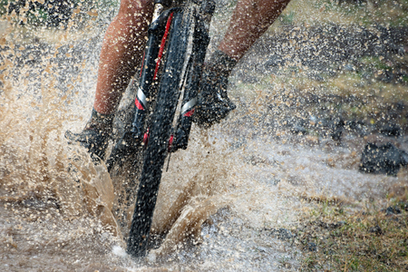 Mountain biker speeding through forest stream. Water splash.