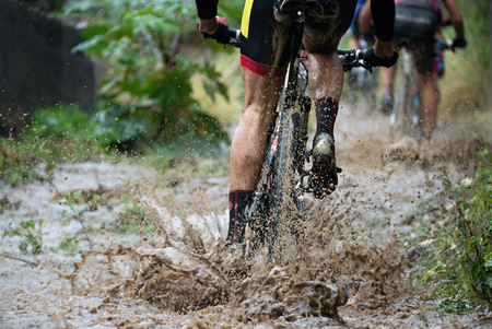 Mountain bikers driving in rain upstream creek Stockfoto