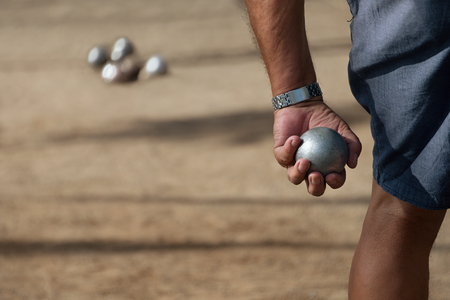 Senior men playing petanque, balls on the ground.