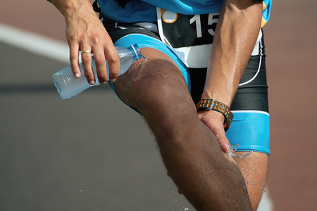 cool down: Athlete pouring water on himself to cool down after running Stock Photo