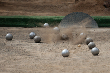 bocce ball: Petanque ball boules bawls on a dust floor,photo in impact