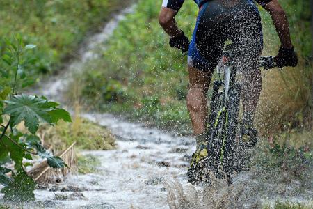 Mountain biker driving in rain upstream creek