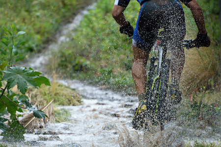 mountain bicycling: Mountain biker driving in rain upstream creek