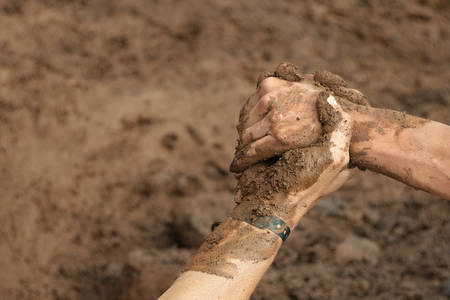 overcoming: Couple hold hands,help when overcoming hindrances mud Stock Photo