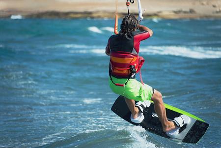 kiteboarding: Kitesurfer flying over the wave.Kitesurfing in blue sea