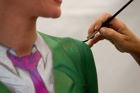 body painting: Body painting in process.Young female nude body art painter