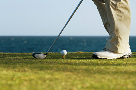 Golfer is going to tee off at sunset, ocean and horizon Stock Photo