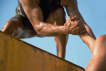 obstacle: Par la mano, ayudar a superar obstáculos cuando el barro Foto de archivo