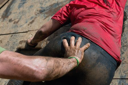 overcoming: Mud race runners.Racing helps when overcoming hindrances