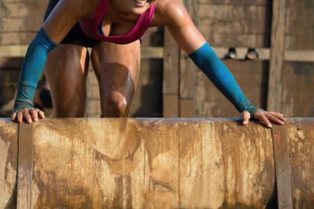 obstacle: corredores de carreras de barro, sonrisa de la mujer a superar el obstáculo Foto de archivo