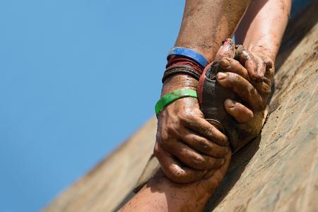 Couple tenir la main, aider lorsque surmonter les obstacles de la boue Banque d'images - 62314078