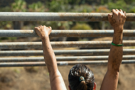 Mud race runners,hands overcome obstacle