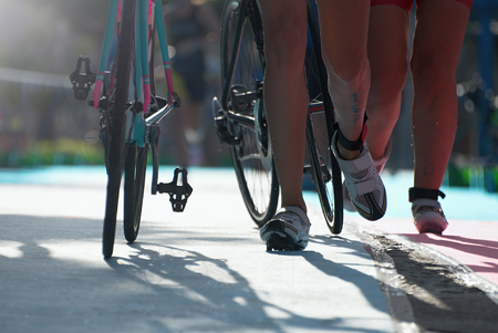 triathlete: Triathlete running with cycle in the transition zone Stock Photo