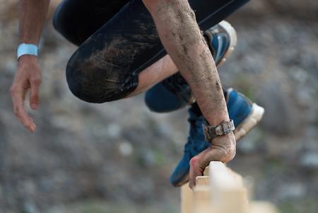 Mud ras lopers, deelnemer springt over obstakels