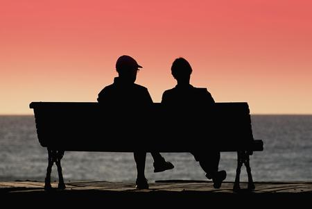 mujer mirando el horizonte: silueta de los pares de la tercera edad a la espera de la puesta del sol colourfull en el banco cerca del océano Foto de archivo