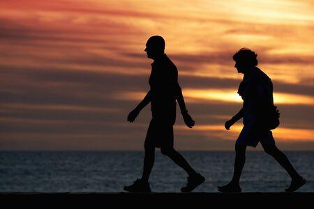 Seniors walking brisk walk along the shore at sunset 写真素材