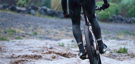 Mountain bikers driving in rain upstream creek 写真素材