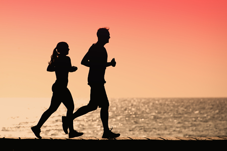 Silhouette man and woman run together on a sunset on sea coast