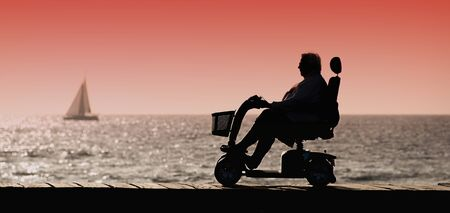 lame: Silhouette of a woman in a wheelchair ride to the coast of the sea Stock Photo