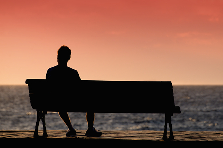 benches: Silhouette of young men sitting alone on the bench in front of the sea