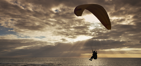 Silhouette of flying paraglider over the sea sunset Stock Photo
