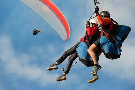 Deux parapentes volent en tandem contre le ciel bleu, parapente tandem guidé par un pilote
