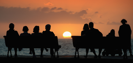 Silhouette of a group of people who sits on the bench, looking at the sunset