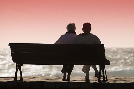 Silhouette seniors couple waiting for colourfull sunset on the bench near ocean Archivio Fotografico