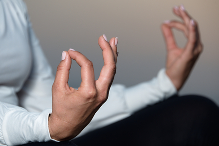 welling: Yoga woman meditating and making a zen symbol with her hand
