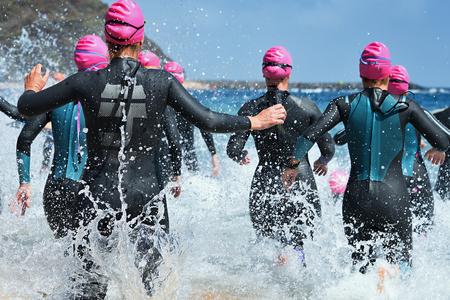Groepstriatlondeelnemers die het water in rennen voor een zwemgedeelte van de race, een scheutje water en atleten die rennen.