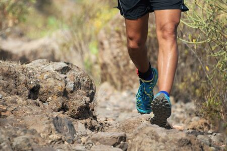 Trail running man on mountain path exercising,workout outdoors on rocky terrain Stock Photo