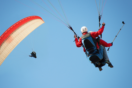Two paraglider tandem fly against the blue sky,tandem paragliding guided by a pilot 写真素材