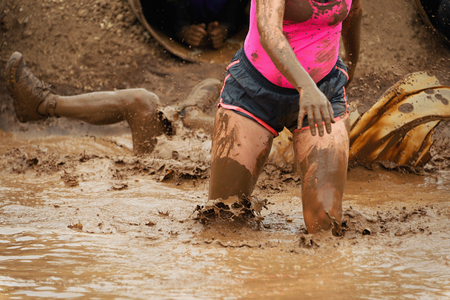 Mud race runners In the background a participant fell in mud Stok Fotoğraf