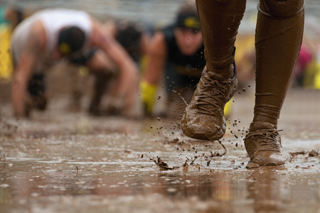 Mud race runners passing under a barbed wire obstacles during extreme obstacle race,detail of the legs
