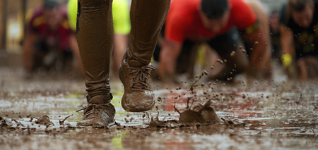 Mud race runners passing under a barbed wire obstacles during extreme obstacle race,detail of the legs Reklamní fotografie - 82793810