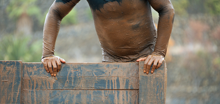 Mud race runners running over obstacles extreme sport Stock Photo
