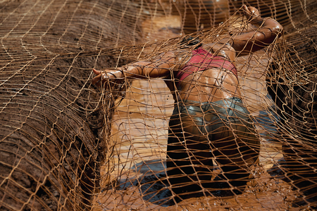 Mud race runners.Woman covered with mud fighting to get out of a net in the obstacle race