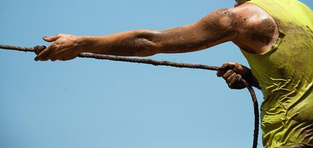 Mud race runners,defeating obstacles by using ropes