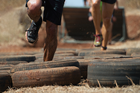 Mud race runners, tries to make it through the tire trap Stock Photo - 84041795