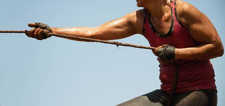 Mud race runners,defeating obstacles by using ropes,tug of war
