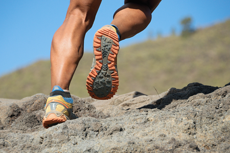 Athlete trail running in the mountains on rocky terrain, sports shoes detail